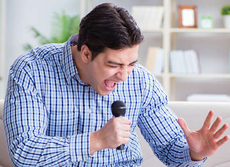 Funny man singing songs in karaoke at home Stockfoto