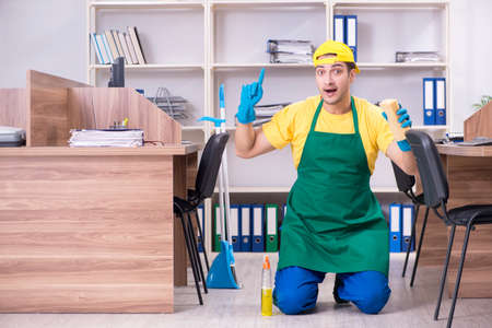 Young male contractor cleaning the office Stockfoto