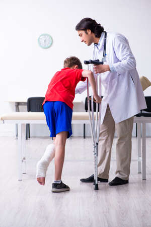 Leg injured boy visiting young doctor traumatologist