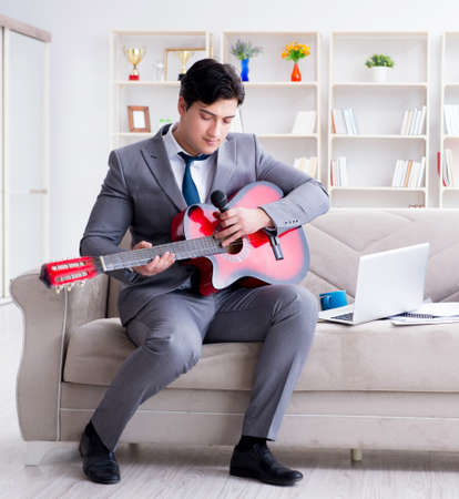Businessman playing guitar at home Banque d'images - 129098265