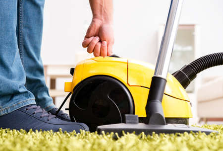 Man cleaning the floor carpet with a vacuum cleaner close up Banque d'images - 129621169