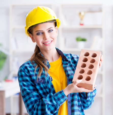 Woman with brick in construction concept
