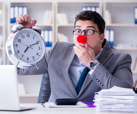 Clown businessman with alarm clock missing dieadline Stockfoto