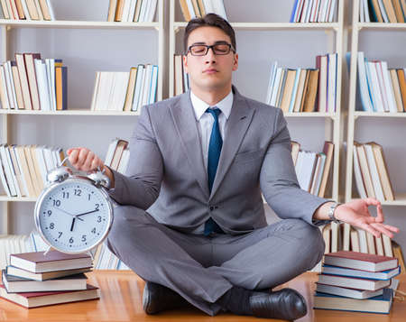 Businessman student in lotus position with an alarm clock in lib