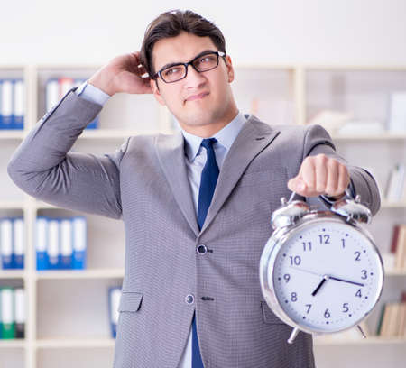 Businessman with alarm clock in the office Stockfoto
