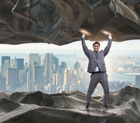 Businessman supporting stone under pressure Banco de Imagens