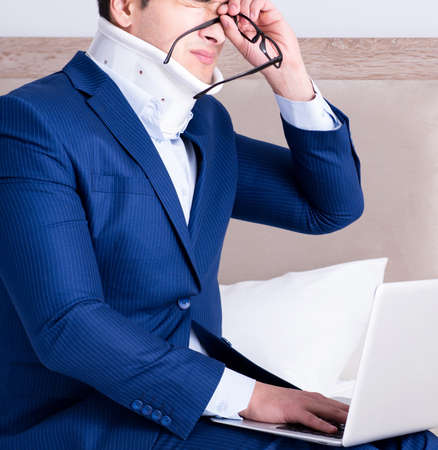 Businessman with neck injury working from home 写真素材
