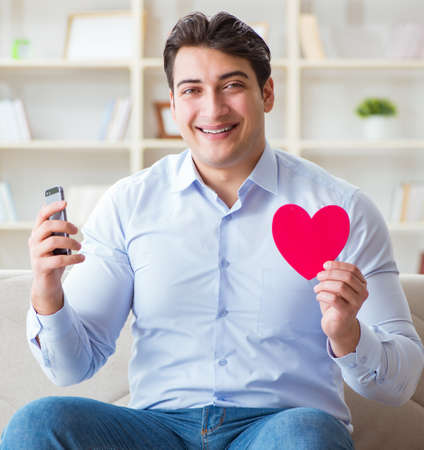 Young man chatting with his sweetheart over mobile phone Stock fotó