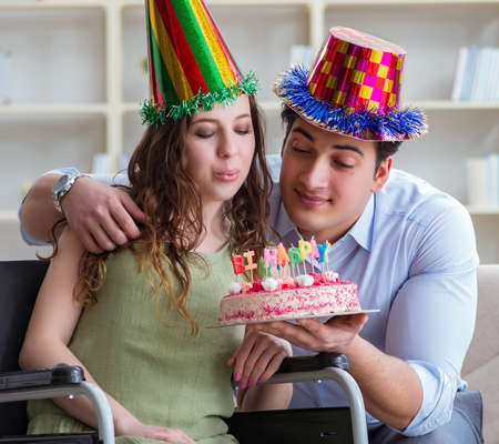 Young family celebrating birthday with disabled person 写真素材