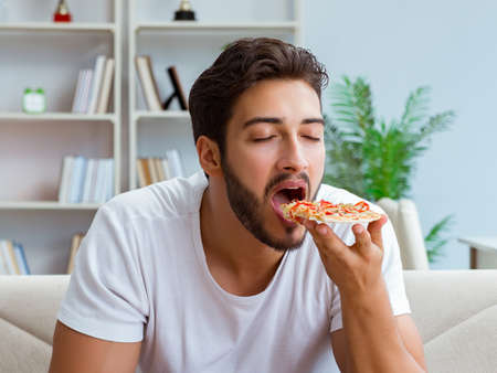 Man eating pizza having a takeaway at home relaxing resting Zdjęcie Seryjne