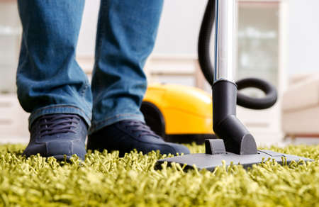 Man cleaning the floor carpet with a vacuum cleaner close up Banque d'images - 129697854