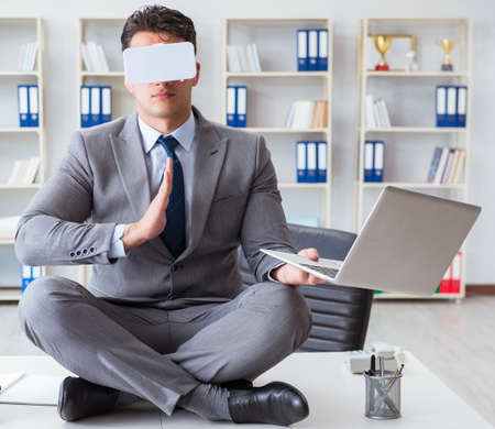 Businessman in virtual reality VR glasses meditating at desk top