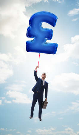 Businessman flying on british pound sign inflatable balloon Imagens