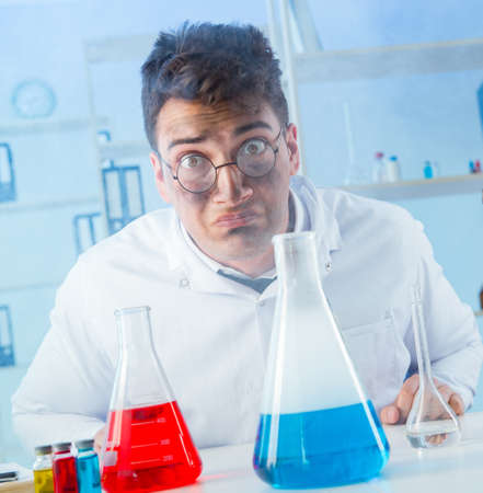 Funny mad chemist working in a laboratory Banco de Imagens