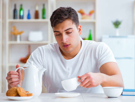 Man falling asleep during his breakfast after overtime work Фото со стока