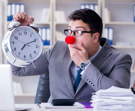 Clown businessman with alarm clock missing deadline