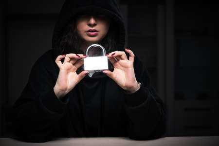 Female hacker hacking security firewall late in office Stockfoto