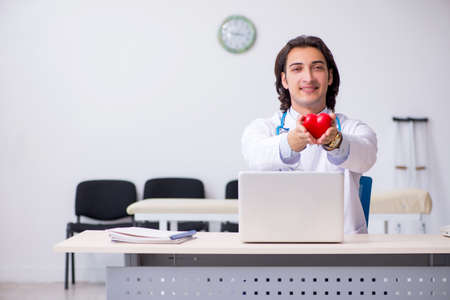 Young handsome doctor cardiologist working in the clinic Stock fotó