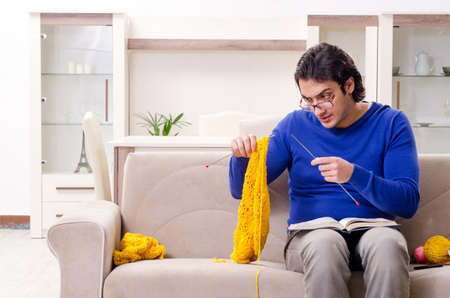 Young good looking man knitting at home Фото со стока