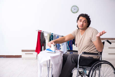 Young man in wheel-chair doing ironing at home Banque d'images - 129615857