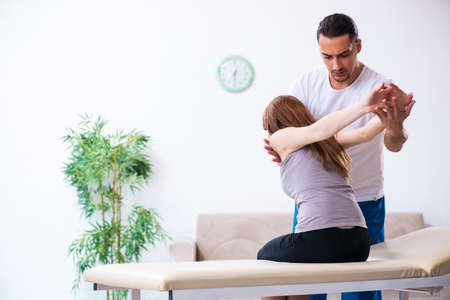 Young woman visiting male doctor physiotherapist