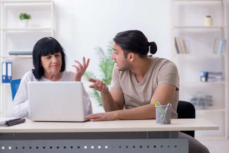 Young male employee explaining to old female colleague Stock fotó