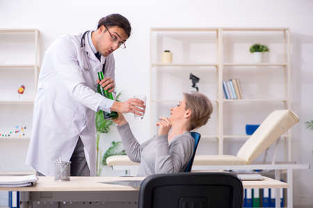 Female alcoholic visiting young male doctor Imagens