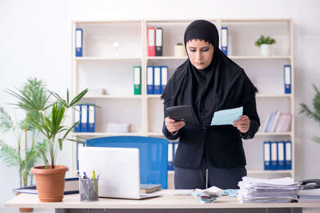 Female employee bookkeeper in hijab working in the office Zdjęcie Seryjne - 129780936