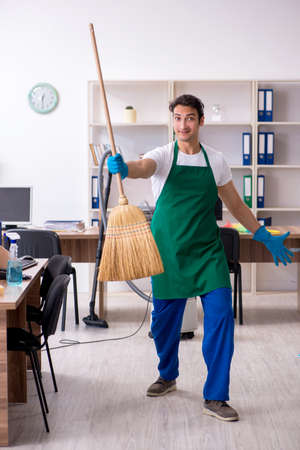 Young handsome contractor cleaning the office Banque d'images - 129666915