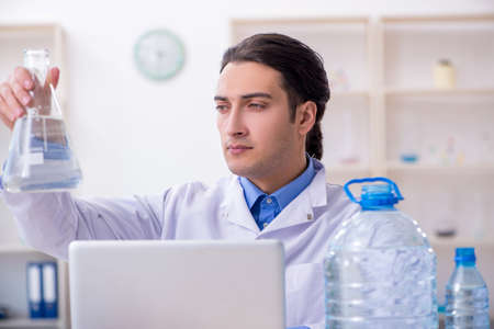 Young male chemist experimenting in lab Zdjęcie Seryjne - 129780962