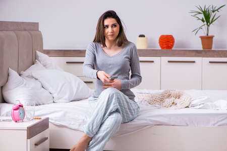 Young pregnant woman in the bedroom
