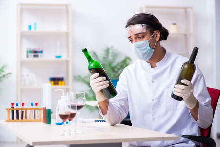 Male chemist examining wine samples at lab Zdjęcie Seryjne - 129795470