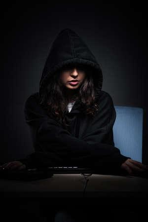 Female hacker hacking security firewall late in office Zdjęcie Seryjne - 129795473