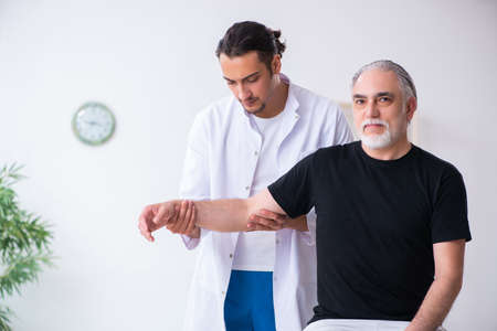 Old injured man visiting young doctor