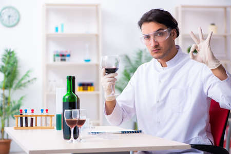 Male chemist examining wine samples at lab 写真素材