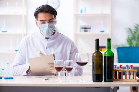 Männlicher Chemiker, der Weinproben im Labor untersucht Standard-Bild