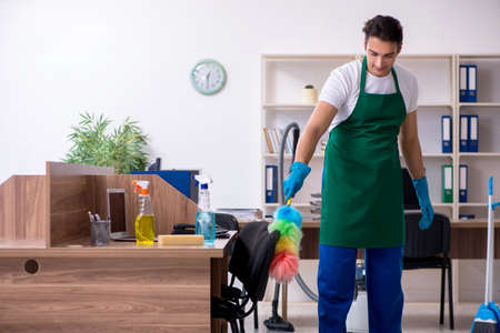 Young handsome contractor cleaning the office Banque d'images - 129699137