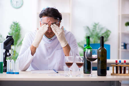 Male chemist examining wine samples at lab 스톡 콘텐츠