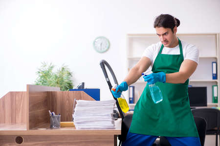 Young handsome contractor cleaning the office Banque d'images - 129595108