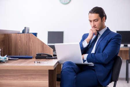 Junger gutaussehender Geschäftsmann, der im Büro arbeitet Standard-Bild
