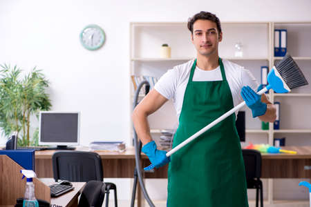 Young handsome contractor cleaning the office Фото со стока - 129922782