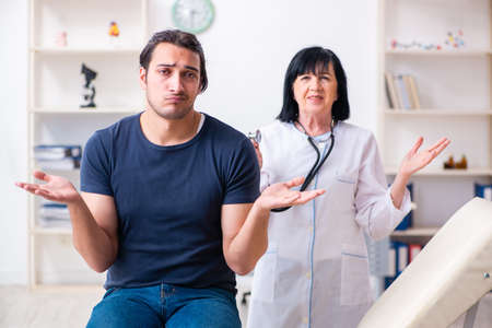 Young male patient visiting aged female doctor Stockfoto - 129700186