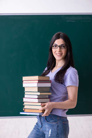 Young female teacher student in front of green board Stock fotó