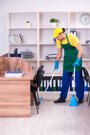Young male contractor cleaning the office Banque d'images - 129700689