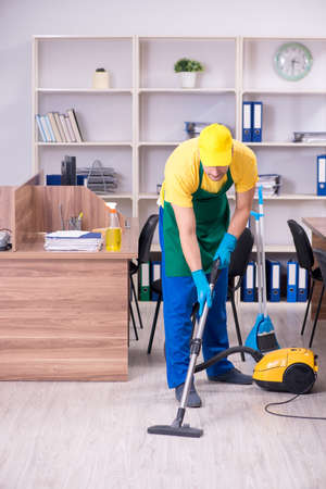 Young male contractor cleaning the office Banque d'images - 129700732