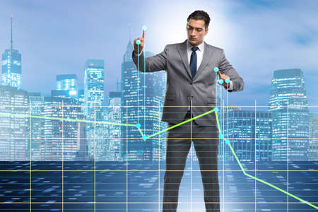 Businessman controlling the market with strings Stock Photo