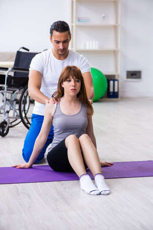Male physiotherapist doing exercises with injured woman on floor Reklamní fotografie