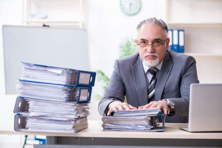 Aged male employee unhappy with excessive work Stock fotó - 129922994