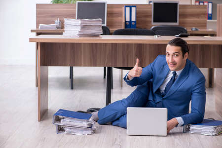 Young male employee and too many work in the office Stock fotó - 129923066