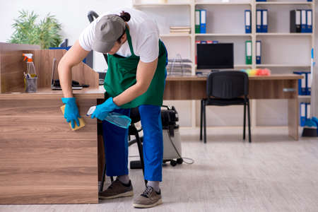 Young handsome contractor cleaning the office Фото со стока - 129923078